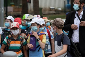School children wearing face masks to help prevent the spread of the coronavirus as they walk in Tel Aviv, July 6, 2020.
