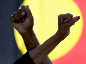 A man and woman cross arms in front of an Aboriginal flag as thousands gather at a rally supporting the Black Lives Matter and Black Deaths in Custody movements in Sydney, Australia, July 5, 2020.