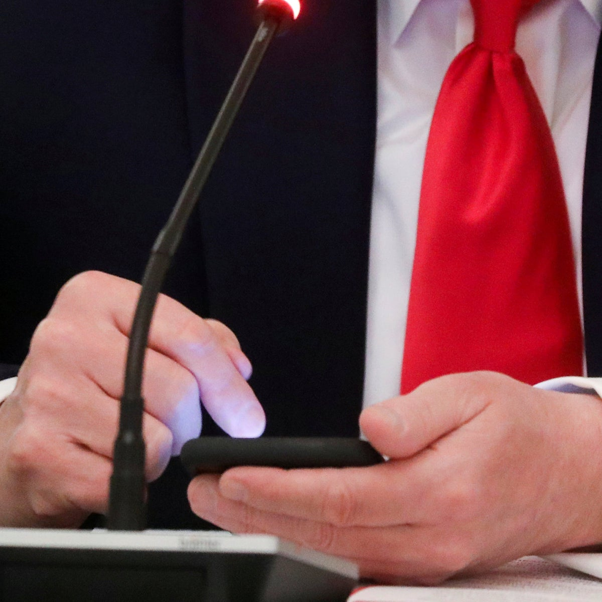 Trump taps the screen on a mobile phone during a roundtable discussion on the reopening of small businesses in the State Dining Room at the White House in Washington, U.S., June 18, 2020.