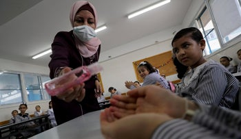 A teacher sanitizes the hands of a student in a classroom at a United-Nations run school in Gaza City, August 8, 2020.