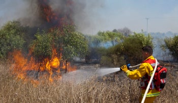 Israeli firefighters put out a blaze caused by incendiary balloons from Gaza near Kibbutz Nir Am, August 7, 2020.