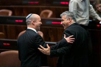 Yamina leader Naftali Bennett and current opposition leader Yair Lapid laugh together in Knesset, July 5, 2014. The two politicians are currently doing well in polls.