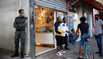 An Israeli police officer enforces coronavirus regulations in Neve Shanaan, a neighborhood of southern Tel Aviv where many asylum seekers live, May 24, 2020.