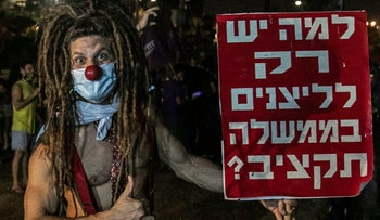 A protester holds a sign that says 'Why is it that only the clowns in government have a budget?' at a demonstration against the Netanyahu government, Tel Aviv, August 1, 2020.