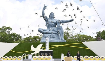 Doves fly over the Peace Statue in Nagasaki's Peace Park during a ceremony commemorating the 75th anniversary of the bombing of the city, August 9, 2020.