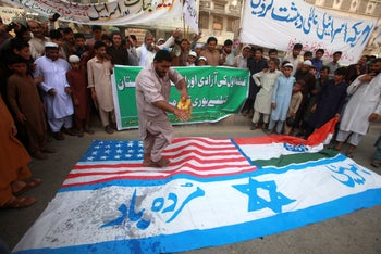 A protester sprinkles petrol to burn representations of Israeli and US flags during al-Quds Day in Peshawar, Pakistan, May 22, 2020. Banner reads 'America and Israel are terrorists.'