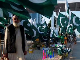 A man waits for transportation next to a roadside stall displaying national flags in Rawalpindi on August 4, 2020, ahead of Pakistan's 74th anniversary of independence from British rule