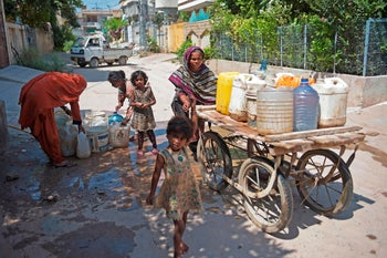 A woman pushes a handcart loaded with drinking water containers on a street in Rawalpindi on July 22, 2020