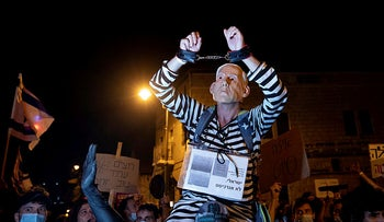 A protester wearing a mask of Prime Minister Benjamin Netanyhau's face in a prison suit and shackles in Jerusalem, August 8, 2020.