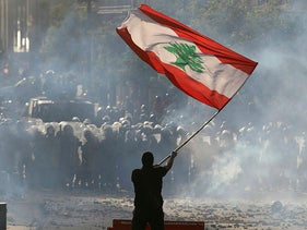 A demonstrator waves the Lebanese flag in front of riot police during a protest in Beirut, Lebanon, August 8, 2020.