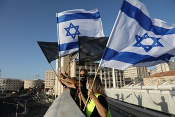 Protesters wave Israeli flags and black flags during an anti-government protest in Jerusalem, August 8, 2020.