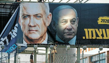 An election campaign banner, showing Benny Gantz and Benjamin Netanyahu, being erected in Ramat Gan in February.