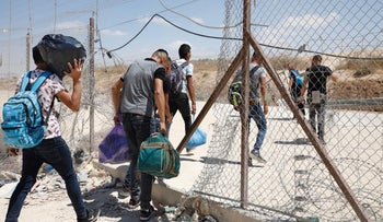 Palestinians pass through a breach in a fence near the Meitar checkpoint in the West Bank, August 9, 2020.