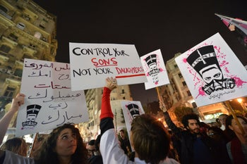 Protesters hold up placards and shout slogans during a demonstration against sexual harassment in Egypt's capital Cairo, February 12, 2013.