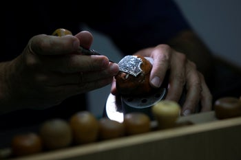 A worker for the Israeli jewelry company Yvel holds a part of a mask in Motza near Jerusalem, August 9, 2020.