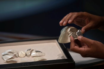 Isaac Levy, owner of Israeli jewelry company Yvel holds parts of a mask in Motza near Jerusalem, August 9, 2020.