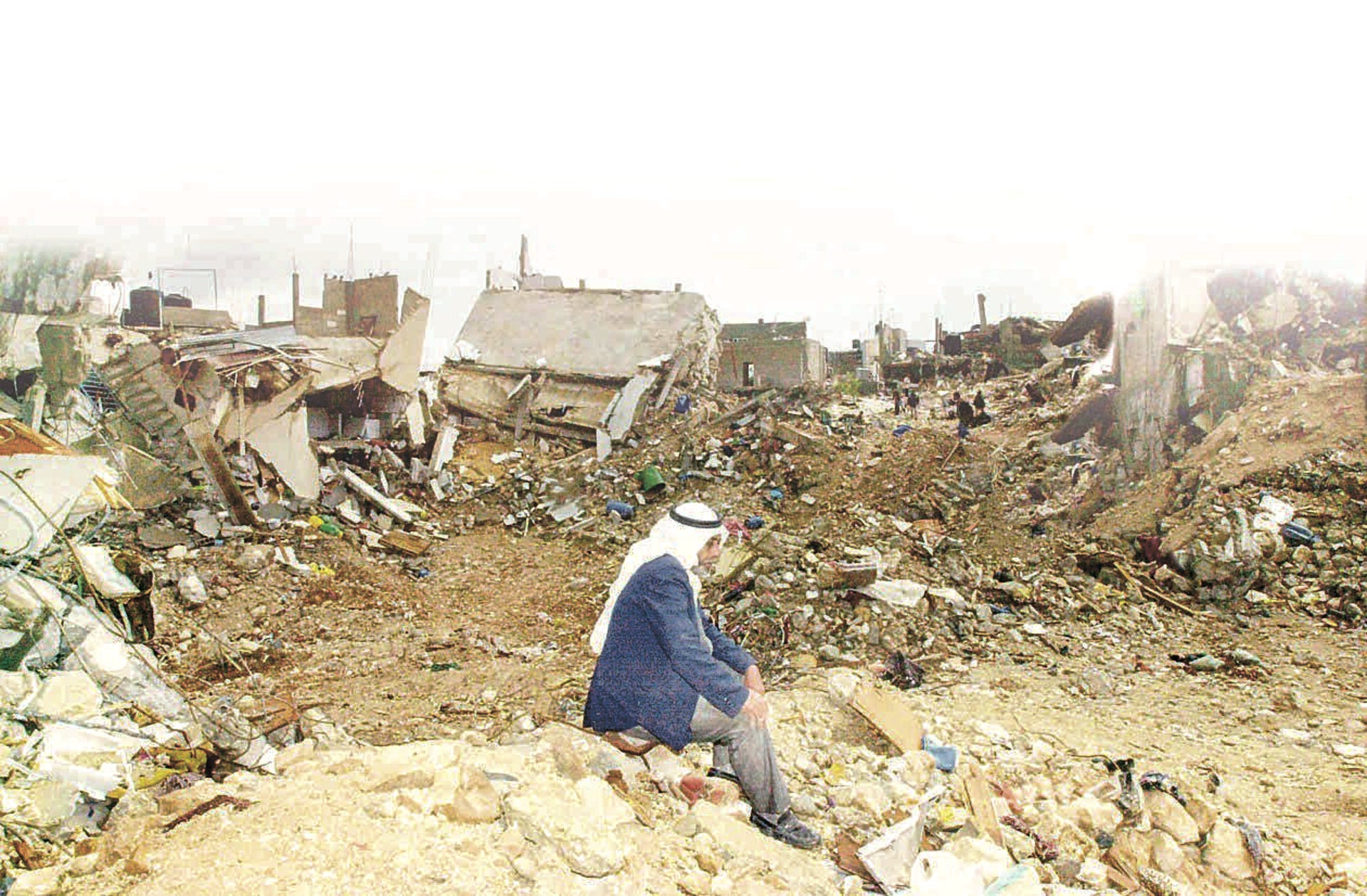 A man is sitting in the rubble in Jenin during Operation Defensive Shield, April 2002.