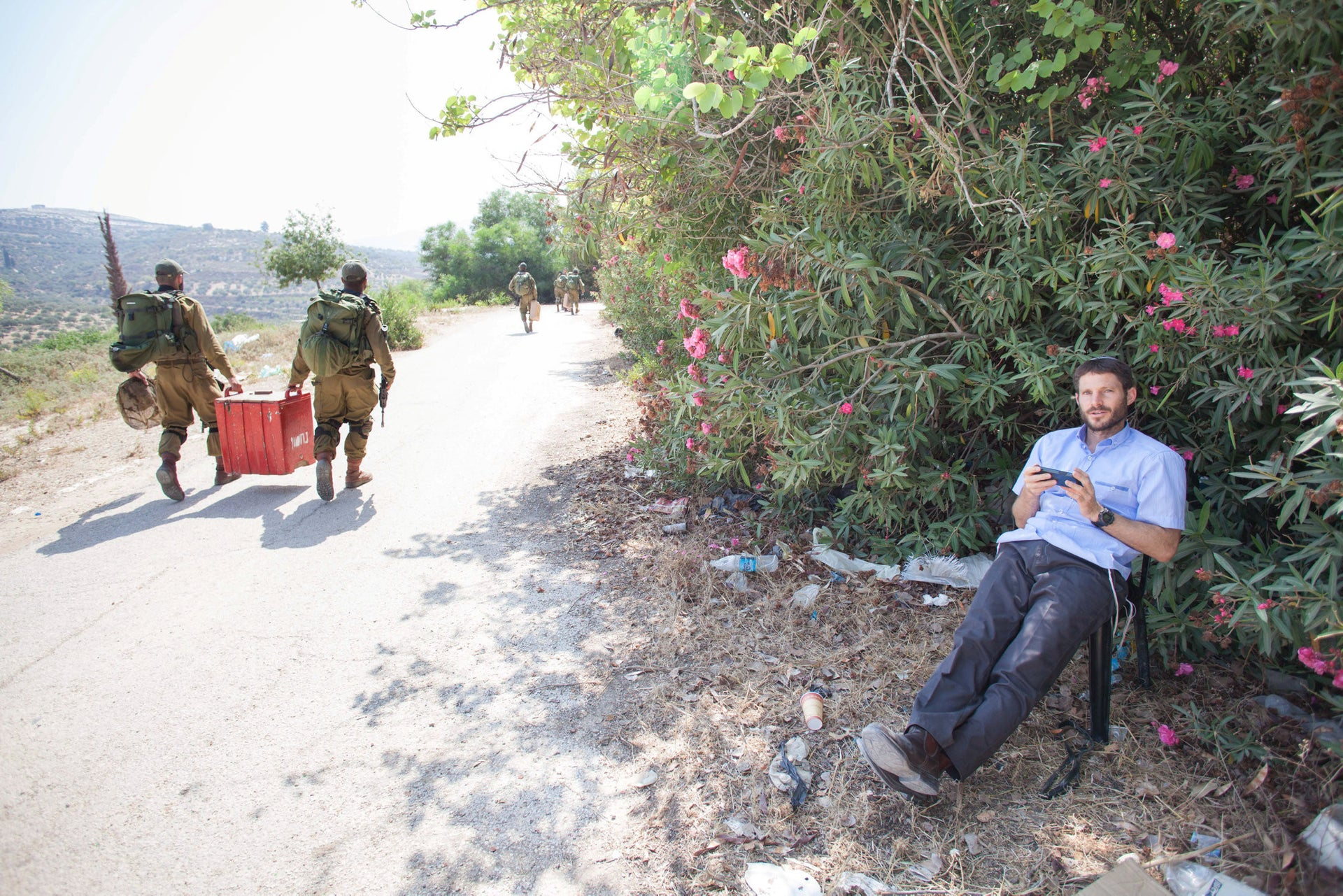 MK Betzalel Smotrich sitting in front of a tree as soldiers walk by in the evicted settlement of Sa Nur.