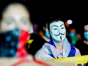 A protester wearing a Guy Fawkes mask stands with an Israeli flag around his neck during a demonstration against the Israeli government, Tel Aviv on August 1, 2020.