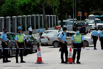 Police officers stand guard outside Apple Daily headquarters as Hong Kong media tycoon Jimmy Lai is arrested by police officers at his home in Hong Kong, August 10, 2020.