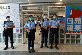 Police stand guard at the entrance of the Apple Daily headquarters in Hong Kong, August 10, 2020.