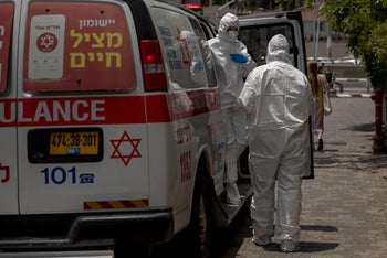 Medical workers wearing protective suits in Tel Aviv, July 2020.