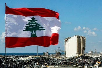 This picture taken on August 9, 2020 shows a Lebanese flag flying along a bridge near the destroyed port of Lebanon's capital Beirut.