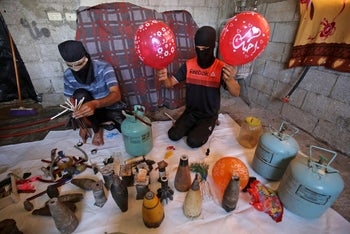 Masked Palestinians prepare flammable objects before attaching them to balloons to be flown toward Israel as incendiary devices. Rafah, southern Gaza Strip. August 8, 2020