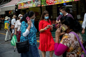 People wearing protective face masks and using their cellphones in Jerusalem, August 10, 2020.