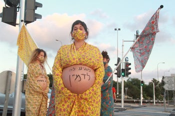 """She deserves to imagine"" it says on Perach Boker's stomach in the protest artwork led by Maya Ben David. Kabri Junction, August 8, 2020."