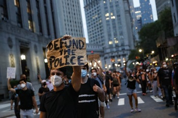 "A demonstrator holding a ""Defund the police"" sign during a protest march in support of Black Lives Matter, New York, July 30, 2020."