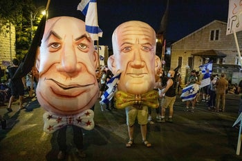 Protesters asking for the government's resignation wear masks of Netanyahu, left, and Benny Gantz, right, Jerusalem, August 8, 2020.