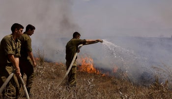 IDF soldiers putting out a fire sparked by incendiary balloons sent from Gaza into southern Israel, August 12, 2020.