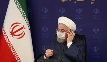 President Hassan Rohani adjusts his face mask in a meeting of the national headquarters of the fight against the COVID-19, in Tehran, Iran, on July 18, 2020.
