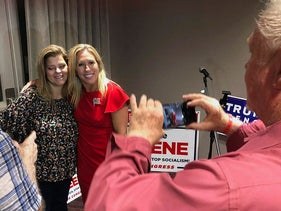 Supporters take photos with construction executive Marjorie Taylor Greene, background right, late Tuesday, Aug. 11, 2020, in Rome, Ga.