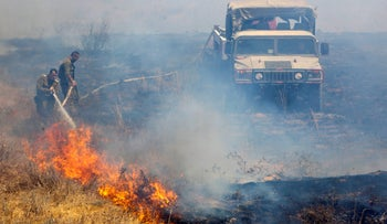 Firefighting soldiers put out a blaze in a Gaza border forest that was started by an incendiary balloon launched from Gaza, August 11, 2020.
