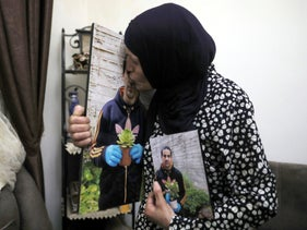 Rana, mother of Eyad Hallaq, kisses his photo in their home in East Jerusalem's Wadi Joz, June 2020.