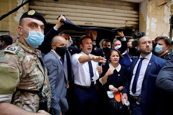 French President Emmanuel Macron gestures as he visits a devastated street of Beirut, August 6, 2020.