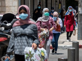 People walk wearing face masks in East Jerusalem, July 15, 2020