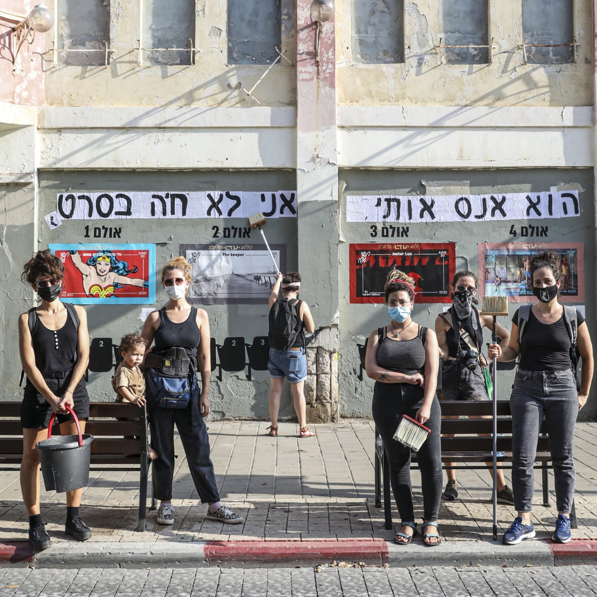 The members of the 'Sticker women' group ('HaStickeriot') in Tel Aviv, August 2020. The sticker behind them reads: 'He raped me, I am not imagining.'