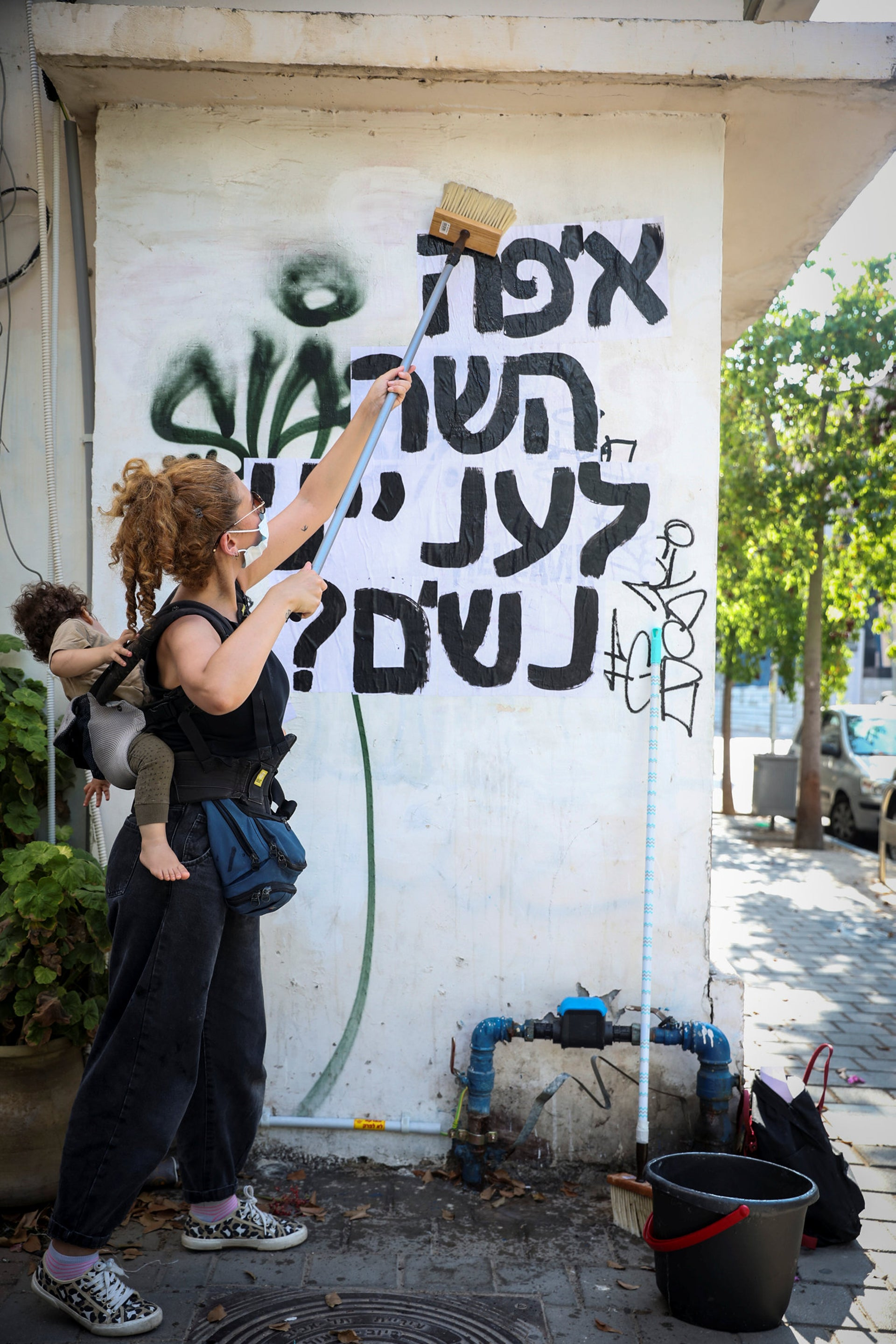 A member of the group is sticking a sign in Tel Aviv that reads 'Where is the Women Protection Minister?'