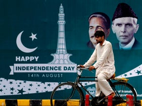 A cyclist passes a Happy Independence Day billboard with images of founder leader Muhammad Ali Jinnah and national poet Allama Muhammad Iqbal. Islamabad, Pakistan, Aug. 13, 2020