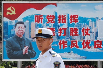 A People's Liberation Army (PLA) Navy soldier stands in front of a backdrop featuring Chinese President Xi Jinping during an open day at a naval base in Hong Kong, China June 30, 2019