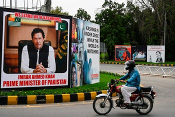 A motorcyclist rides past a billboard displaying a picture of Pakistan's Prime Minister Imran Khan declaring his support for Kashir along a street in Islamabad on August 4, 2020