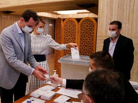 In this photo released on the official Facebook page of Syrian Presidency, Syrian President Bashar Assad and his wife Asma vote at a polling station in the parliamentary elections in Damascus, Syria, Sunday, July 19, 2020