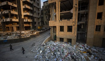 People walk next debris from destroyed buildings near the site of last week's explosion that hit the seaport of Beirut, Lebanon, August 12, 2020.