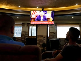 A television screen shows Donald Trump as Palestinians follow the news on the UAE's agreement with Israel on normalizing relations, in Hebron, August 13, 2020.