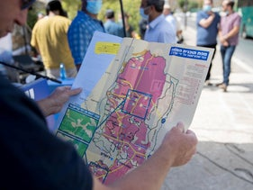 Settler leader inspects a map of proposed West Bank annexation as part of Trump's Middle East plan at a rally in Jerusalem, June 21, 2020.