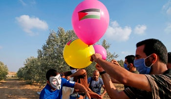Masked Palestinians prepare to attach an incendiary device to balloons before releasing them near Gaza's Bureij refugee camp, by the Israel-Gaza border fence, August 12, 2020.