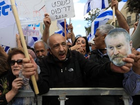 Netanyahu supporters protest outside the Jerusalem District Court on May 24, 2020, with a sign reading 'Dreyfus trial 2020' and a photo of Attorney General Avichai Mendleblit.